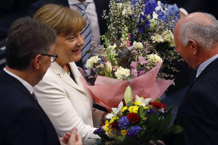 A chanceler alemã Angela Merkel recebe flores no Parlamento logo após a aprovação de seu novo mandato
