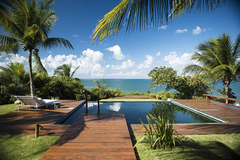A piscina tem o formato quadrado, medindo cerca de cinco metros em cada lado. Ela é rodeada por um deque de madeira, onde há uma cadeira de sol. Esta área tem visão para o mar, que aparece no fundo da imagem