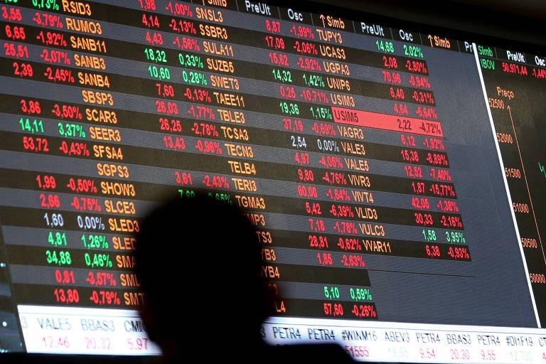 Pessoas acompanham painel de informações com gráficos de desempenho das ações na BM&F Bovespa