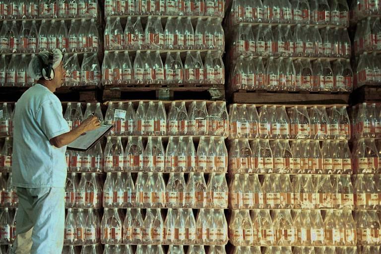 Funcionário em fábrica de água mineral; homem se encontra em frente a pilhas de água engarrafada