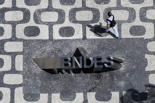 FILE PHOTO: Man walks past the logo of Brazilian Development Bank (BNDES) at the entrance of its headquarters in Rio de Janeiro
