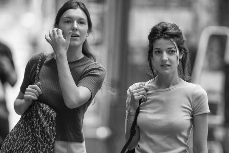 """Foto preto e branco mostra duas moças, uma alta e mais loira (Louise Chevillote, que vive Ariane) e uma mais baixa e mais morena (Esther Garrel, que vive Jeanne), caminhando na rua lado a lado, em cena do filme """"Amante por um Dia"""", de Philippe Garrel"""