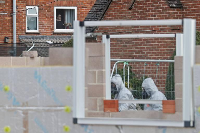 Mulher observa enquanto militares com roupas de proteção retiram veículo relacionado ao envenenamento de ex-espião russo em Salisbury, na Inglaterra