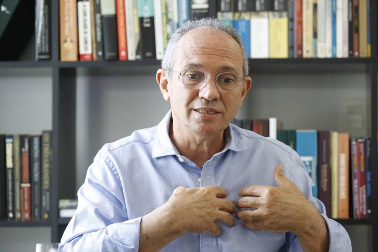 O governador do Espírito Santo, Paulo Hartung, concede entrevista em sua casa em Vila Velha (ES). Está de óculos, camisa azul clara. Atrás dele uma estante de livros.