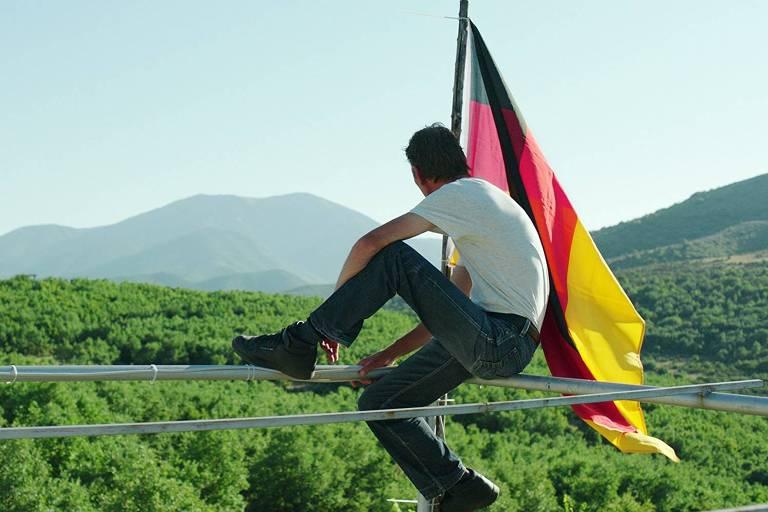 Um homem sentado de costas sobre um parapeito mira uma vista verde, cheia de árvores e, ao fundo, montanhas; ao lado dele, uma bandeira da Alemanha