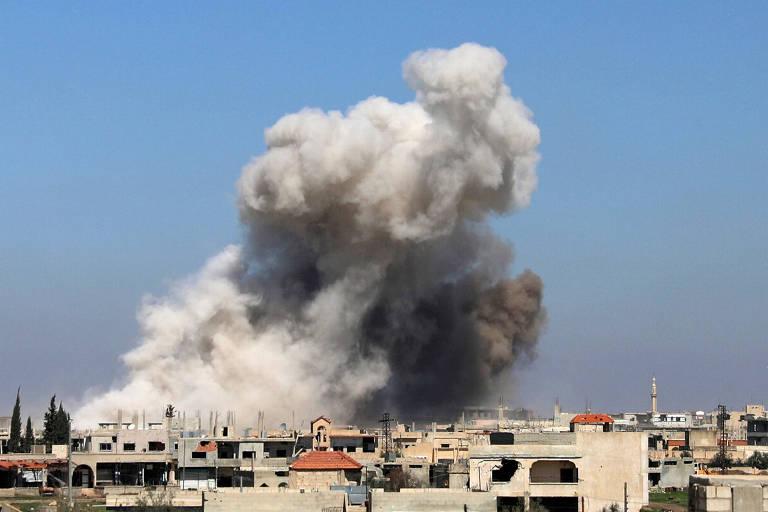 Fumaça sobe de região alvo de bombardeio em Busra al-Harir, perto de Deraa, cidade onde começaram os protestos que deram origem à guerra na Síria
