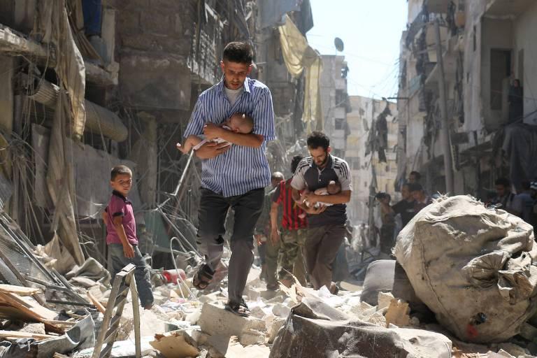 Homens carregam dois bebês e tentam sair dos escombros dos prédios de uma rua do bairro de Salihin, em Aleppo, em 2016