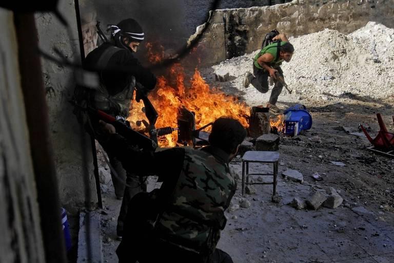 Grupo de rebeldes das Brigadas al-Tawhid correm para tomar posições durante ataques das forças do regime ao bairro de Al-Amariya, em Aleppo, em 2012
