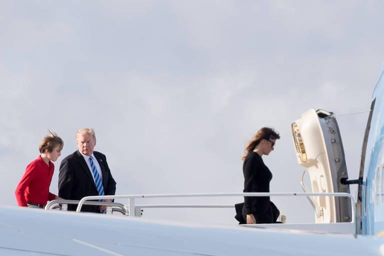 Donald Trump, seu filho Barron (de vermelho) e a primeira-dama Melania embarcam no avião presidencial na Flórida