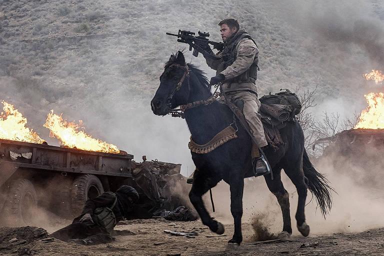 """Chris Hemsworth em cena de """"12 Heróis"""", montado em um cavalo e com uma arma na mão"""
