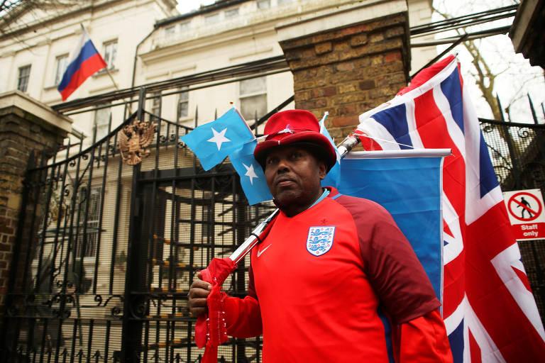 Homem com uniforme da seleção inglesa de futebol segura bandeira britânica em frente ao consulado russo em Londres