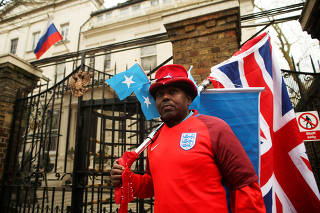 A man wears an England football shirt and holds a Union flag as he stands outside Russia's consular section in London