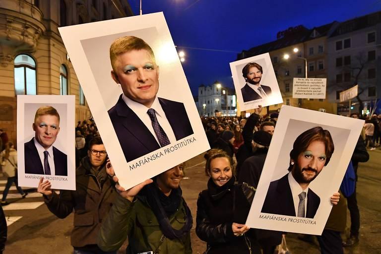 Manifestantes em Bratislava carregam cartazes com o rosto pintado do premiê Robert Fico (esq.) e do ministro Robert Kalinak