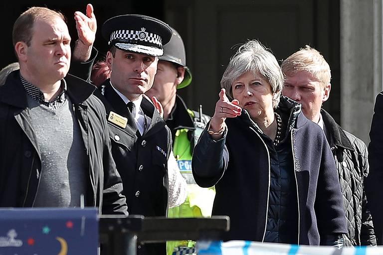 A primeira-ministra britânica Theresa May conversa com o chefe da polícia do condado, Kier Pritchard (de chapéu)