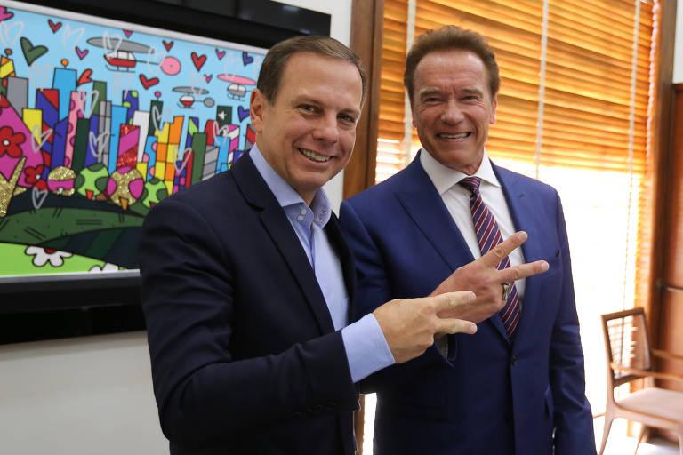 O prefeito João Doria faz seu símbolo conhecido como 'acelera' ao lado do ator Arnold Schwarzenegger