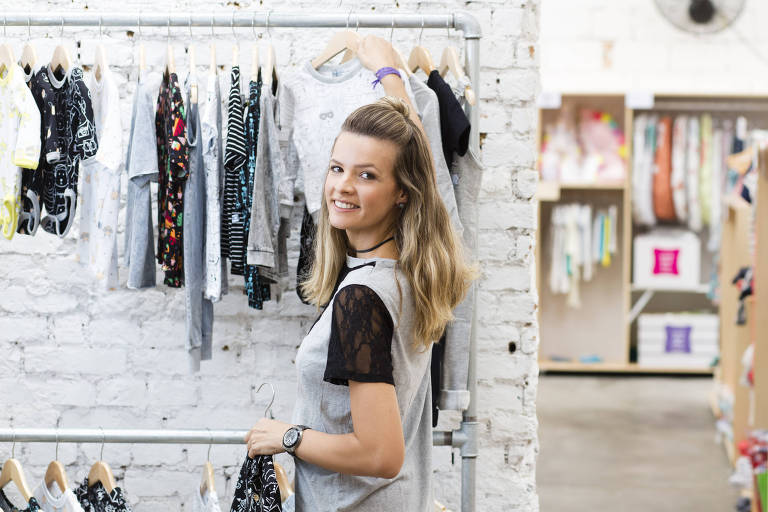 3ee6d68a0 Mulher de roupa cinza pendura roupas numa arara contra uma parede branca