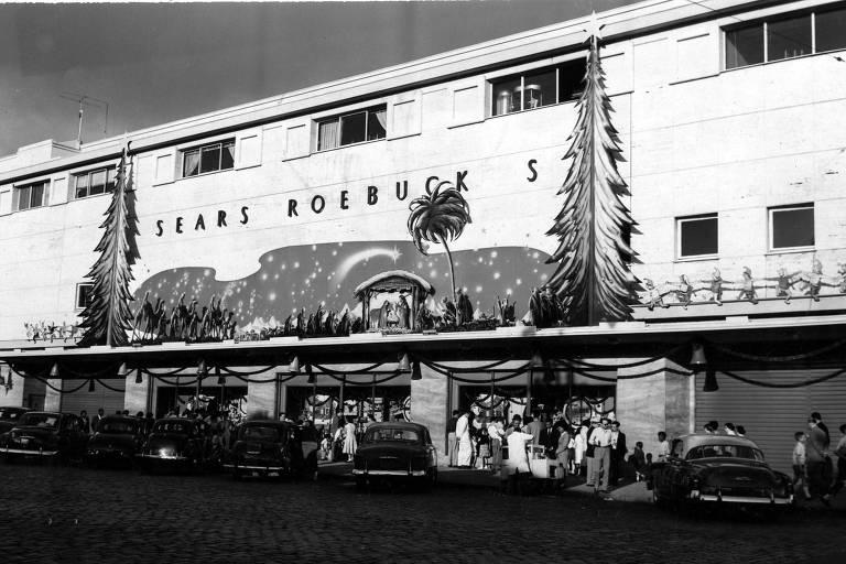 """Fachada da Sears, em São Paulo, prédio branco com decoração natalina e um letreiro onde se lê """"Sears Roebuck"""""""