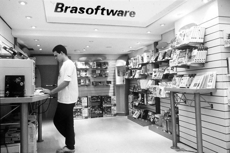 A loja da Brasoftware em imagem de 1996, com uma pessoa no canto esquerdo usando um computador e produtos como CD-ROMs dispostos nas prateleiras