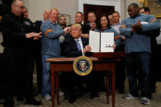 U.S. President Donald Trump signs a presidential proclamation placing tariffs on steel and aluminum imports while surrounded by workers from the steel and aluminum industries at the White House in Washington