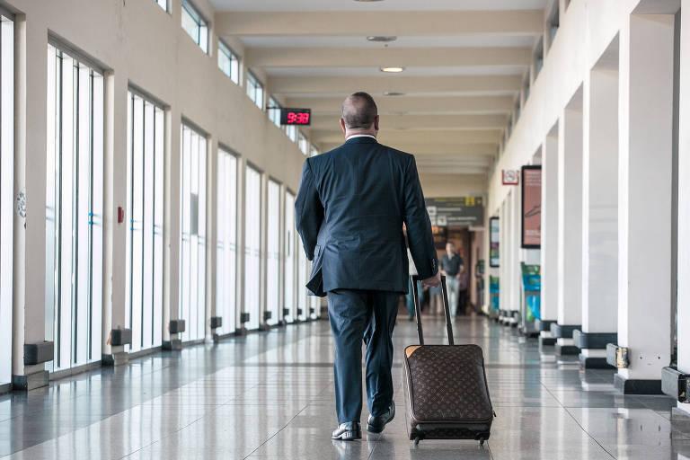 Homem de terno, de costas, puxa mala em corredor de aeroporto