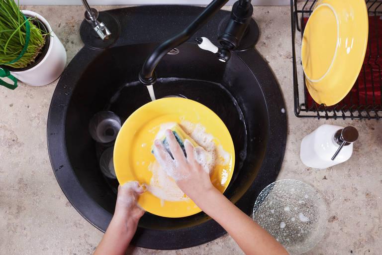 Pessoa lava louça com luvas em pia da cozinha