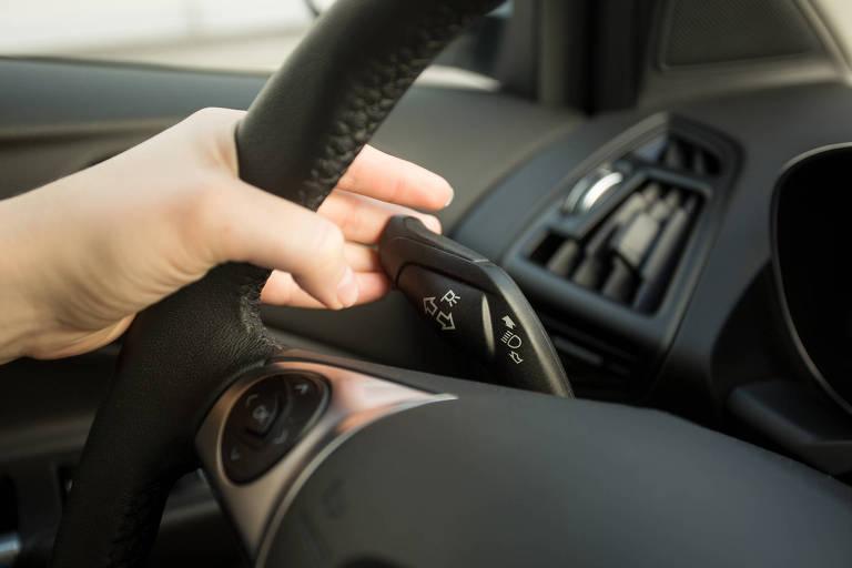 Uma pessoa segura a alavanca de seta atrás do volante de um carro