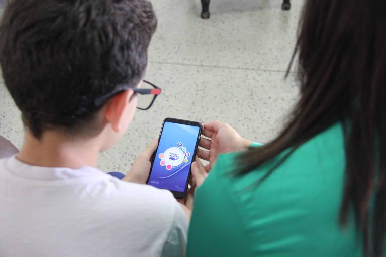 Lays Toledo e seu filho Bruno Toledo usam o aplicativo Palma da Mão