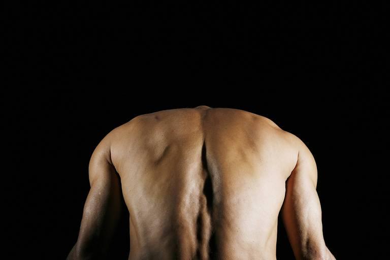 Em frente a um fundo escuro, vemos as costas de uma pessoa, que aparenta curvar-se
