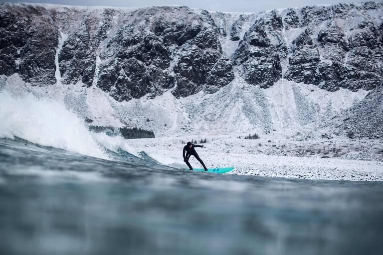 Surfe e aurora boreal na Noruega