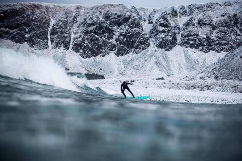 TOPSHOT - A surfer rides a wave on March 10, 2018 in Unstad, northern Norway, Lofoten islands, within the Arctic Circle as air temperature drops minus 13°C and water temperature above 4°C. / AFP PHOTO / OLIVIER MORIN
