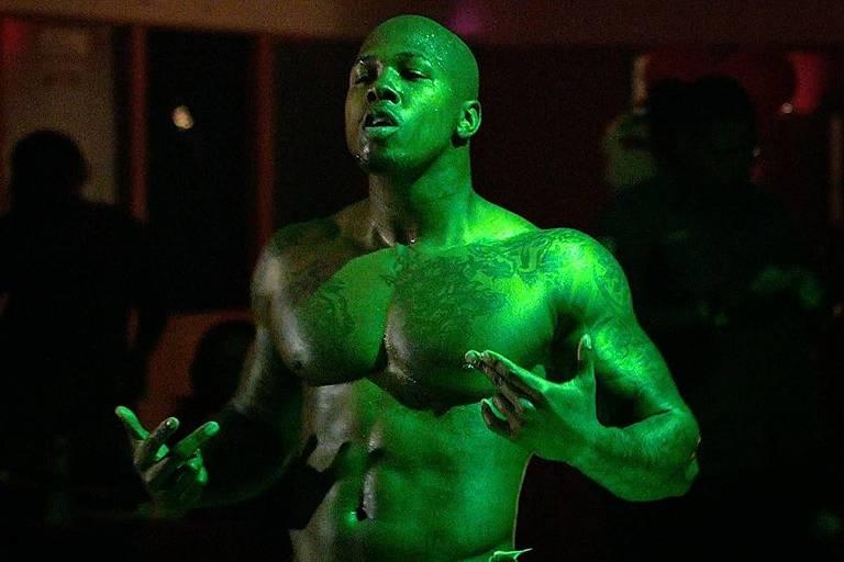 """Homem de torso nu iluminado com luz verde brilhante em cena do documentário  """"This One's for the Ladies"""", exibido no SXSW"""