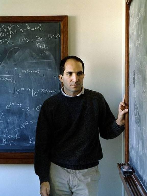 O físico argentino Juan Maldacena entre duas lousas com expressões matemáticas