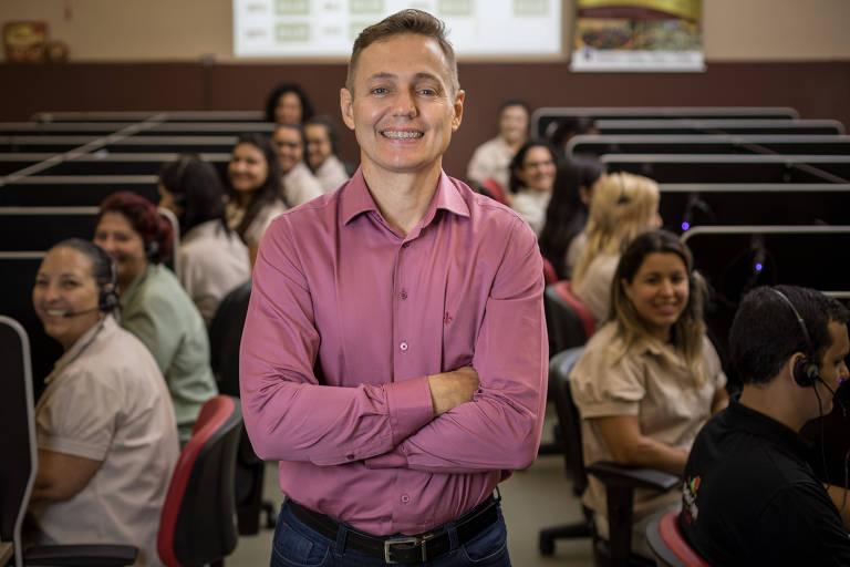 Guto Covizzi, diretor da rede de pizzarias Bella Capri, de braços cruzados call center da empresa com profissionais atrás dele
