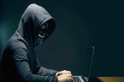 Side view of person wearing hooded top and Guy Fawkes face mask using laptop ORG XMIT: IPTC last updated on 01/03/16 ***PARCEIRO FOLHAPRESS - FOTO COM CUSTO E CRÉDITO OBRIGATÓRIO. PARA OBTER ESTA IMAGEM EM ALTA, ENVIE PEDIDO PARA PESQUISA@FOLHAPRESS.COM.BR***