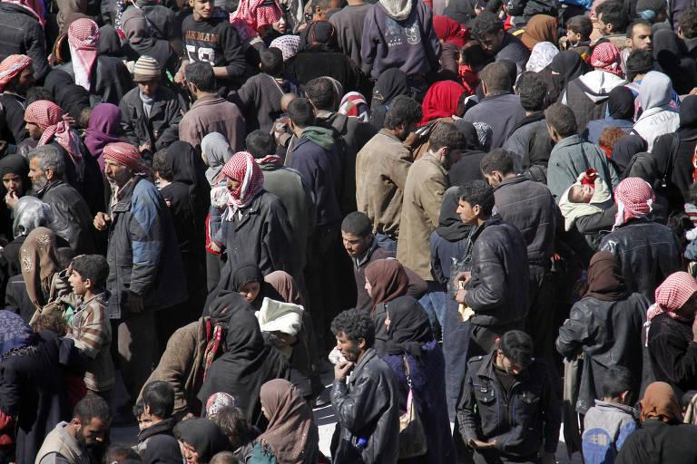 Grupos de civis sírios de casaco e mulheres são vistos do alto esperando em local aberto por transporte
