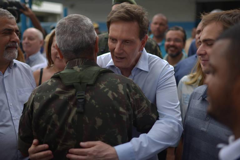 Na Vila Kannedy, o prefeito do Rio, Marcelo Crivella, abraça o general Braga Netto, que fez sua primeira aparição pública após o assassinato da vereadora Marielle Franco