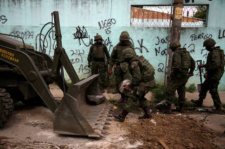 An armed forces members remove barricades during an operation against drug dealers in Vila Kennedy slum in Rio de Janeiro