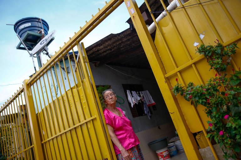 Luiza Maria da Cruz, 80, no portão amarelo que dá acesso à sua casa; ao fundo, uma caixa d'água