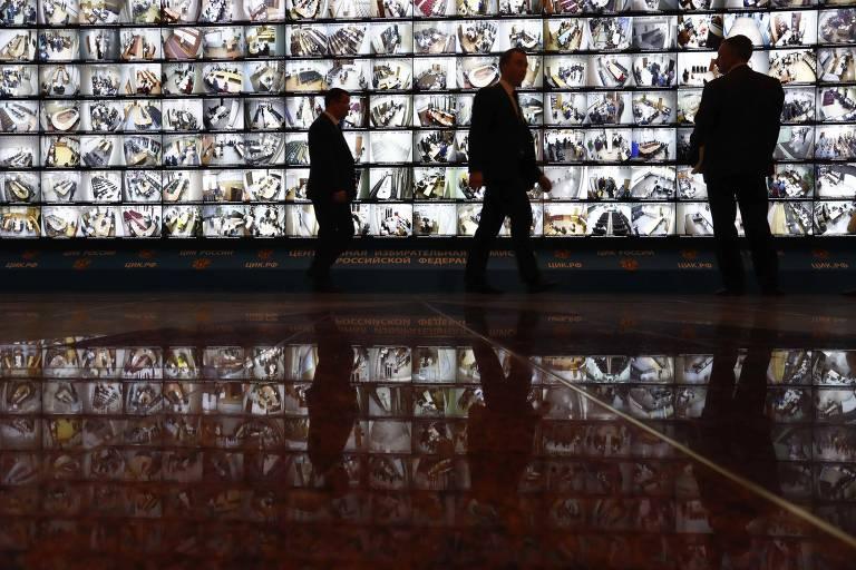 Homens em fronte a telas que transmitem em tempo real a imagem dos locais de votação da eleição russa