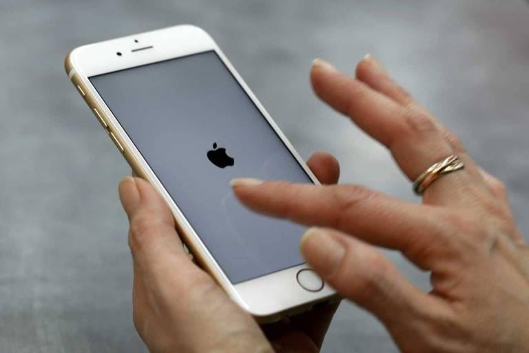 Mulher, com o dedo indicador, usa celular