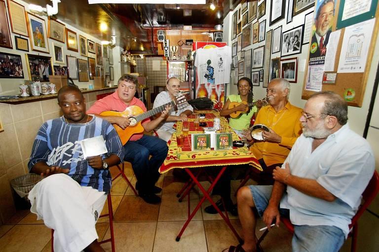 """Foto mostra seis pessoas em volta de uma mesa numa roda de samba no bar """"Bip Bip"""", em Copacabana, no Rio de Janeiro"""