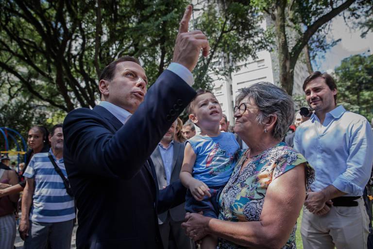 Doria aponta para o alto ao lado de eleitora e criança durante inauguração da reforma da praça 14 Bis, no centro de São Paulo, no dia seguinte às prévias que definiram sua candidatura pelo PSDB ao governo de São Paulo