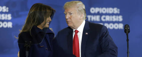 President Donald Trump clasps hands with first lady Melania Trump as he takes the podium to speak about his plan to combat opioid drug addiction at Manchester Community College, Monday, March 19, 2018, in Manchester, N.H. (AP Photo/Elise Amendola) ORG XMIT: NHEA109