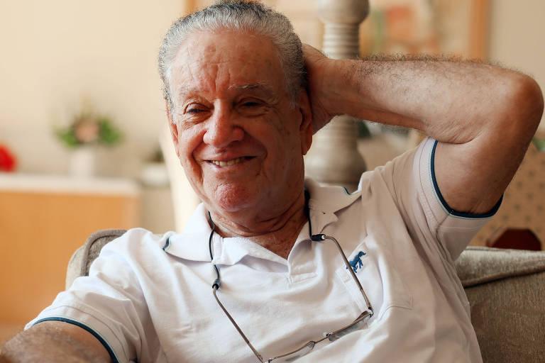 Carlos Caboclo alisa o cabelo com a mão esquerda enquanto concede entrevista para a Folha
