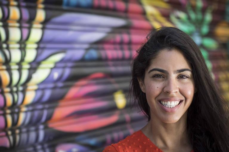 Retrato de Bela Gil sorridente em frente a um grafite de flores