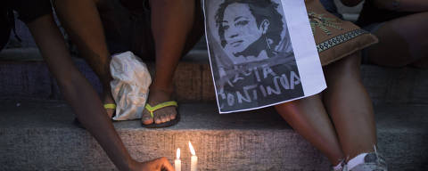 A demonstrator places a candle during a protest against the murder of councilwoman Marielle Franco in Rio de Janeiro, Brazil, Friday, March 16, 2018. Franco was slain Wednesday night while returning from an event focused on empowering young black women. (AP Photo/Leo Correa) ORG XMIT: XLC105