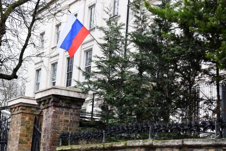 Bandeira tremula ao lado de árvores em frente ao prédio da embaixada da Rússia em Londres