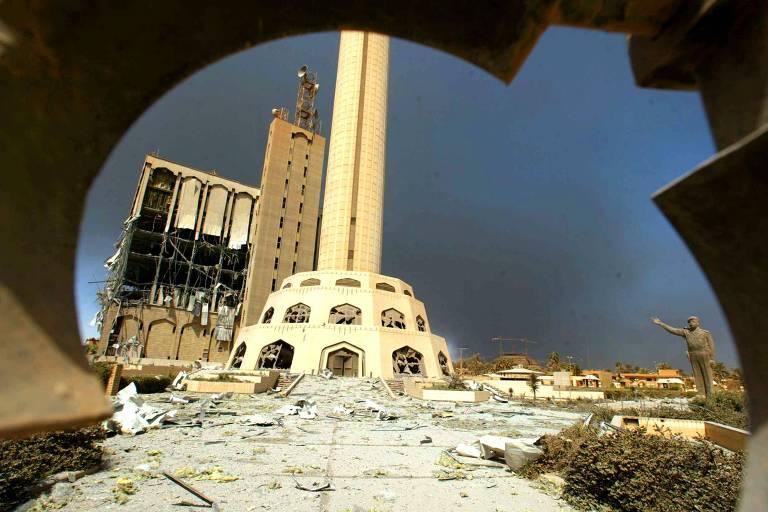 Prédio destruído onde funcionava central de telecomunicações; à direita, estátua de Saddam Hussein