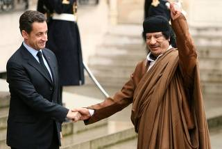 File photo of France's President Nicolas Sarkozy greeting Libyan leader Muammar Gaddafi in Paris