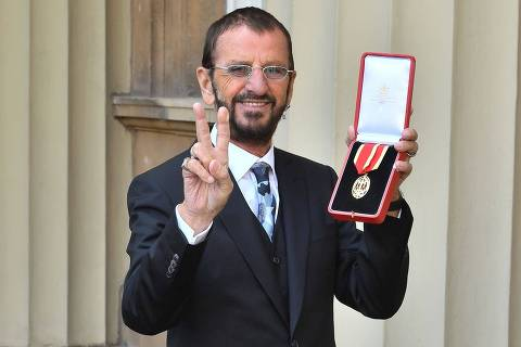 TOPSHOT - Richard Starkey, better knonwn as Ringo Starr, poses with his medal after being appointed Knight Commander of the Order of the British Empire at an investiture ceremony at Buckingham Palace in London on March 20, 2018.  / AFP PHOTO / POOL / John Stillwell